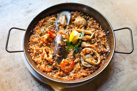 Paella Marinera Traditional, classic spanish main dish paella with shrimp mussels calamares white fish. Aged frying pan with rice, seafood lemon and herbs, up view selective focus