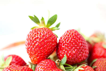 Macro view ripe red strawberries. Fresh berries with green leaves on white background. Shallow depth of field photography Stock Photo