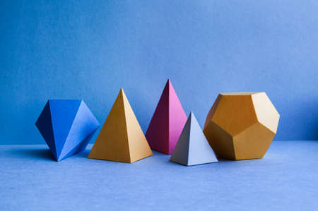 Abstract geometric figures. Three-dimensional dodecahedron pyramid tetrahedron cube rectangular objects on blue background. Bright platonic solids still life background 스톡 콘텐츠