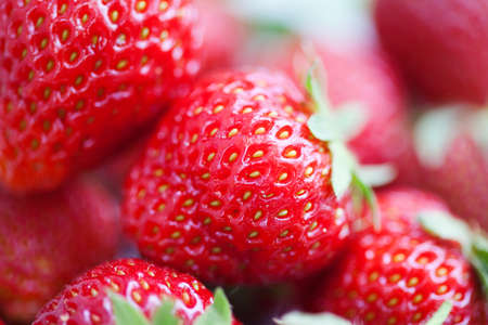 Beautiful strawberry background. Macro view red fresh berry with green leaf. Shallow depth of field photography