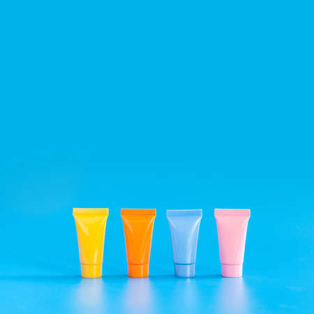 Cosmetic tubes on blue background. Yellow orange blue pink color abstract plastic containers, hygiene products packaging design poster template. Copy space photography.