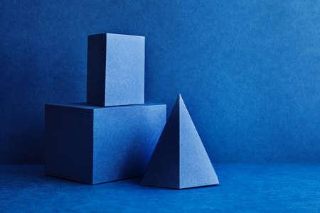 Geometrische Figuren Stillleben Zusammensetzung. Dreidimensionale rechteckige Würfelobjekte der Prismenpyramide Tetraeder auf blauem Hintergrund. Platonische Körperfiguren, Einfachheit Konzeptfotografie Standard-Bild