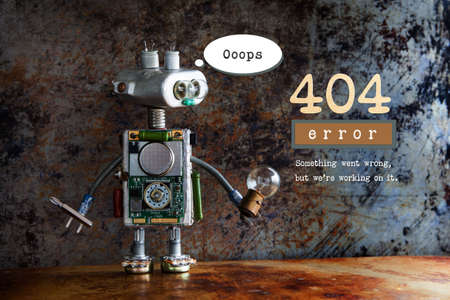 404 error page not found. Robot handyman with screw driver and light bulb on aged metalic background. Text message Something went wrong but we are working on it. Banque d'images