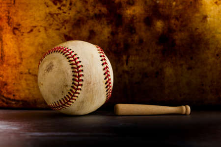 Vintage baseball and small wooden bat. Sport equipment on retro style metal texture background. copy space. Stock Photo