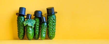 Comical green Cucumbers family on yellow background. Five funny vegetables with black old fashioned hats. Creative design food poster template. Copy space.