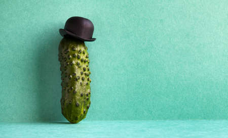Comical mister Cucumber on green background. Funny vegetable old fashioned character with black bowler hat. Creative design food poster template. Copy space.