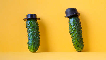 Funny cucumbers old fashioned characters with black hats. yellow background, creative design food poster.