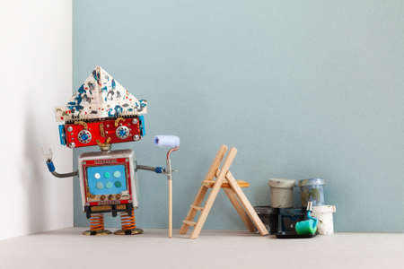 Smiley robot painter decorator with paint roller buckets and wooden ladder. Renovation interior apartment concept Stock Photo