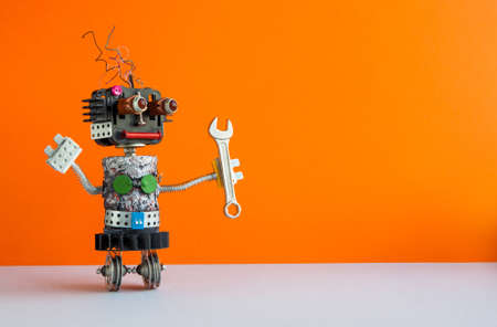 Robot handyman with hand wrench. Fixing maintenance concept. Creative design mechanic two weels robotic character. Orange wall, gray floor background. Copy space.