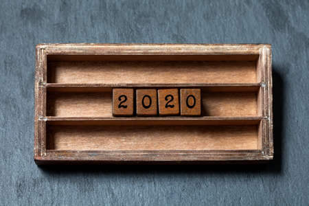 2020 new year retro style card. Two thousand and twentieth year number, wooden cubes in box shelf. 2020 year simplicity design greeting invitation. Gray stone background 版權商用圖片