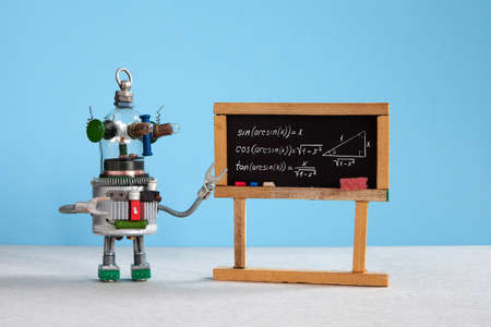 Artificial intelligence and trigonometry lesson in college. Robot teacher explains theory inverse trigonometric functions. Classroom interior with handwritten formula black chalkboard. Blue gray colorful background.