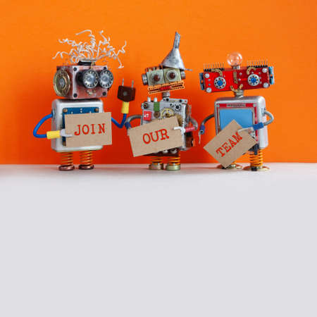 Robotic hiring recruitment concept. Three funny robots looking for a new assistant in company. Hr cyborgs holds a cardboard posters handwritten text Join Our Team. Orange gray background, copy space