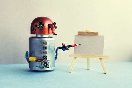 Artificial intelligence robotic concept. Funny robot artist begins to create a drawing with a pencil. White paper template, wooden easel. Advertising poster studio school of visual arts. copy space Imagens