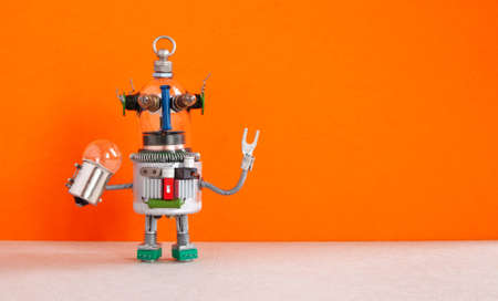 Fantastic robot handyman with light bulb. Fixing maintenaance concept. Creative design robotic toy, silver metallic body. Orange background. Copy space. Stockfoto