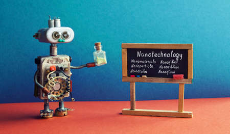Robot scientist holds test tube, explains Nanotechnology innovation industry. Black chalkboard with phrases nanotube, nanomaterials nanofiber etc. Blue wall, red floor classroom interior. Banco de Imagens