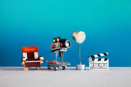 Zone des coulisses du cinéma avec chaise de réalisateur, caméra ou caméscope sur roues, projecteur d'éclairage, projecteur et clap. Réalisation de films en coulisses. Banque d'images