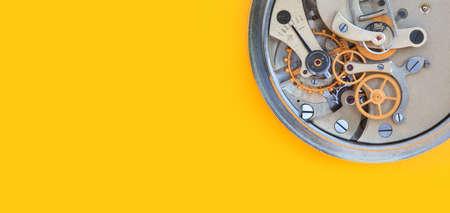 Mechanischer Stoppuhr-Chronometer-Mechanismus, Federbronze-Zahnräder Makroansicht. Geringe Schärfentiefe, selektiver Fokus. Gelber bunter Hintergrund. Platz kopieren Standard-Bild