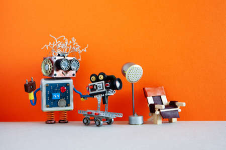 Robot cameraman shoots motion picture television episode or movie. Funny robotic filmmaker operator with retro camera, director chair and spotlight behind the scenes. Orange background copy space.