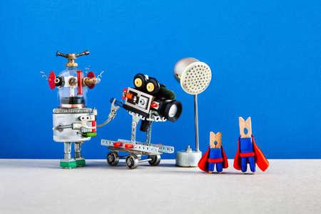 Superhelden-Motion-Film hinter den Kulissen. Beliebter Blockbuster-Bild-Backstage-Bereich mit Hauptrolle Superhelden-Wäscheklammer-Schauspieler, Roboter-Kameramann, Camcorder auf Rädern, Scheinwerfer