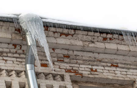 Icy downpipe with icicles, aged roof frame. Cold winter weather concept. copy space.