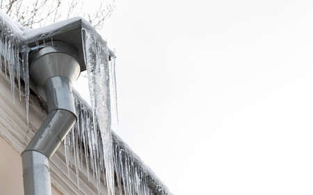 Icy downpipe with icicles, aged roof on white background. Cold winter weather concept. copy space.