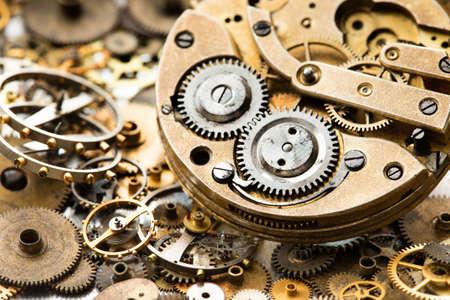 Reloj de bolsillo vintage con piezas de mecanismo de relojería y vista macro de reloj de mano. Fondo de engranajes de metal con textura grunge oxidado. Poca profundidad de campo.