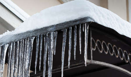 Icicles spike of ice hanging from the snowy roof. Winter subfreezing weather or spring snowbreak concept Stockfoto