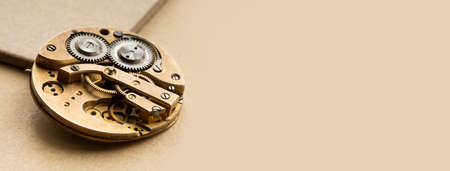 Retro pocket watch mechanic clockwork mechanism, spring bronze cogs wheels macro view. Shallow depth of field, selective focus. Brown background, copy space.