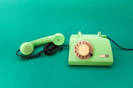 Telefono retrò di colore verde, ricevitore di plastica occupato su sfondo verde Archivio Fotografico