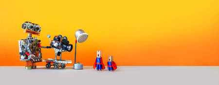 Comical art. Toy robot cameraman makes a movie about super heroes. Funny clothespin actors, robotic operator, camcorder spotlight. Filmmaking behind the scenes concept. Yellow background, empty space.