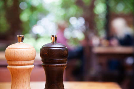 Wooden salt and pepper shakers on blurred defocused background. shallow depth of field and copy space.