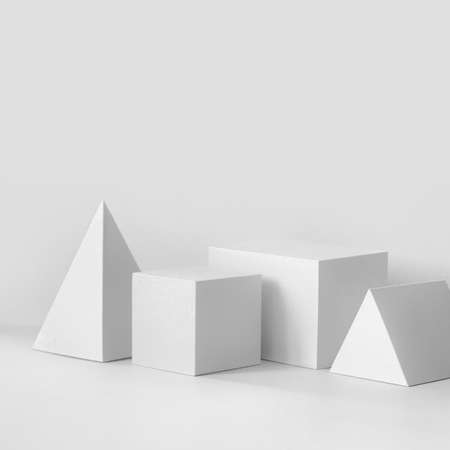 White geometrical figures still life composition. Prism pyramid rectangular cube objects, copy space.