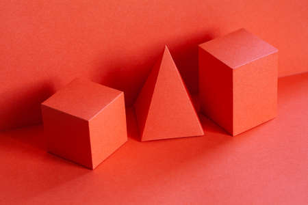 Living coral trend color geometrical figures still life composition. Beautiful three-dimensional pyramid rectangular cube objects. Platonic solids figures, simplicity concept photography