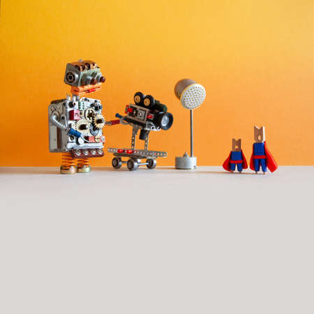 Comical robotic toy cameraman makes a happy ending movie about super heroes. Funny clothespin actors, robotic operator, camcorder spotlight. Yellow orange wall, gray floor background, empty space.