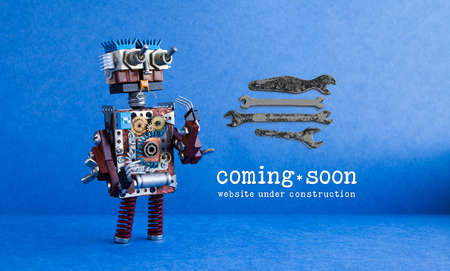 Web site under construction Coming Soon page. Toy robot looks at a set of hand wrenches for maintenance repairs and service works. Blue background