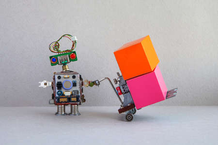 Robotic cargo shipment and courier service concept. Funny toy robot carries a trolley with large multi-colored parcel boxes. gray beige background, copy space on boxes 版權商用圖片