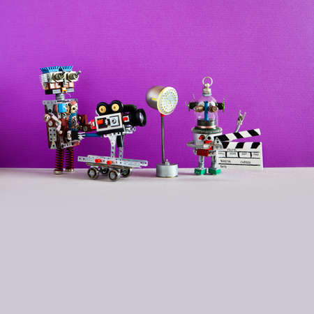 Professional robot cameraman and clapperboard assistant shoots dramatic comedy with elements of a horror movie. Motion picture robotics filmmaking backstage. Purple wall gray background copy space.