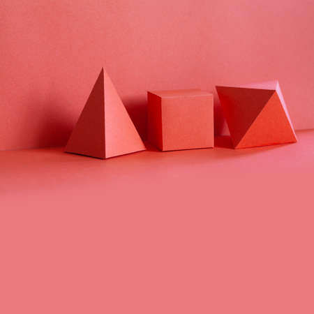 Pink color geometrical figures still life composition. Beautiful three-dimensional pyramid rectangular cube objects. Platonic solids figures, simplicity concept photography. copy space. 写真素材