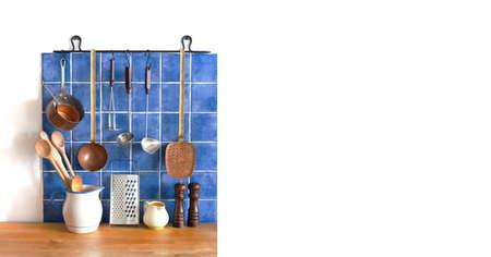 Retro kitchen still life interior. Brass utensils, chef accessories. Hanging copper kitchenware set. Spoon, skimmer, grater. Blue tiles ceramic wall. pitcher, spices on wooden table. White copy space. Archivio Fotografico