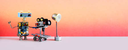 Robotic filmmaking. Funny robot cameraman operator shoots television movie or motion picture. Automated process of creating video content. Pink gray studio background. copy space.