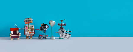 Robotic filmmaking backstage concept. Two robots shoots motion picture television episode or movie. Funny filmmakers director cameraman, cyborg assistant clapperboard on blue background, copy space.