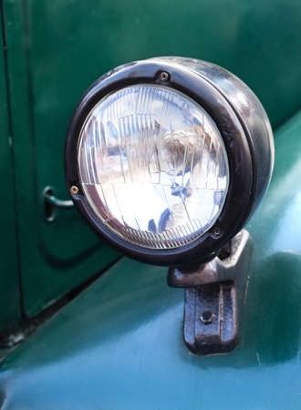 Old style dark green truck lamp. Vintage automobile front side. Closeup. soft focus.
