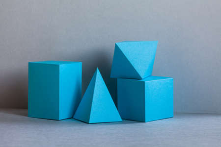 Platonic solids figures geometry. Abstract turquoise color geometrical figures still life composition. Three-dimensional prism pyramid rectangular cube objects on gray background 免版税图像