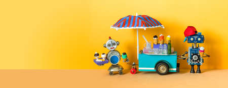Ice cream mobile cart. Summer shop with big umbrella. Robot sell ice cream and cold lemonade. Sandy yellow beach background. copy space.