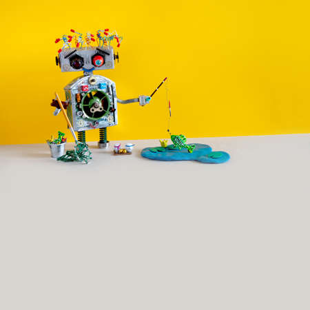 Robot angler fisherman with fishing rod catches fish in a pond. blue lake, water lily, yellow gray background, copy space. Reklamní fotografie