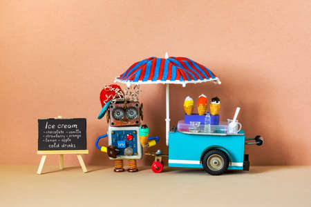 Smiling robot shopman sells cold drinks and ice cream waffle cones. A toy ice cream cart, blackboard shop menu on wooden easel