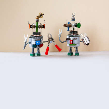 Repair service concept. Two robots are ready for maintenance. Robotic toy handymans with red pliers hand wrench on beige white background. copy space.