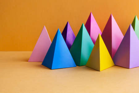 Colorful geometric abstract still life composition. Bright prism pyramid triangle shape figures. Violet yellow blue pink green red color objects, orange background
