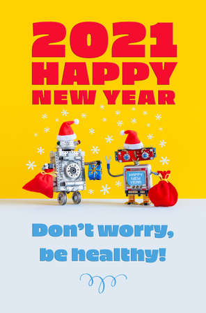 2021 Happy New Year festive robotics congratulation poster. Funny kind robots Santa Claus Noel dressed red Santa hats, Xmas bags gifts. Greeting wish Dont worry, be healthy Yellow gray background 写真素材