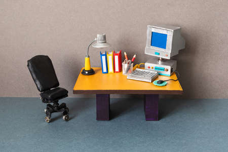 Retro style office workplace. Vintage toy computer, empty blue screen monitor, pc mouse keyboard, archive files. Desk lamp. Comfortable black leather manager chair. Imagens